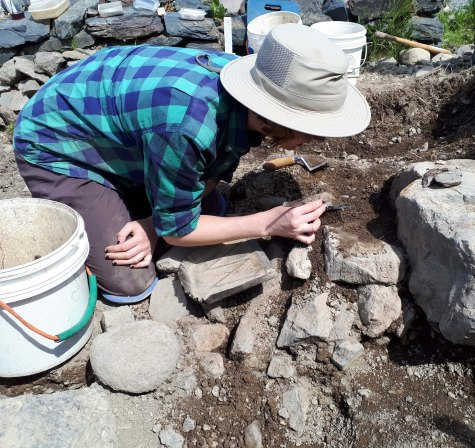 Author removing charred faunal remains from between 17th-century rubble. Photo by Rebecca Jones, 2017